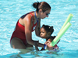 lifeguard teaching child to swim